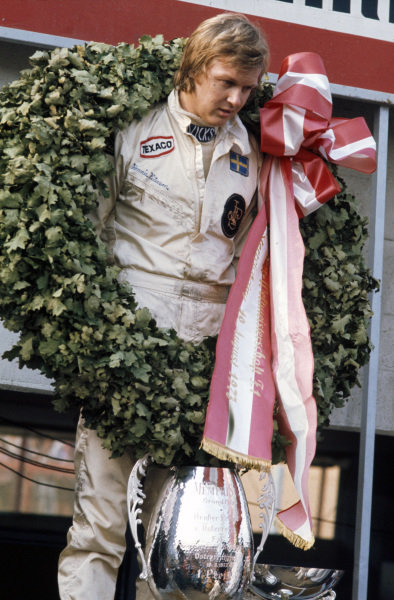 Winner Ronnie Peterson on the podium with his trophy.