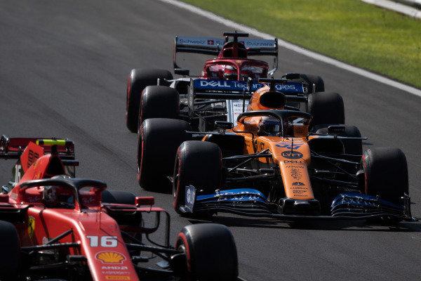 Charles Leclerc, Ferrari SF90, leads Carlos Sainz Jr., McLaren MCL34, and Kimi Raikkonen, Alfa Romeo Racing C38