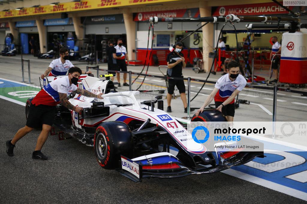 Mechanics push the Mick Schumacher Haas VF-21 in the pit lane