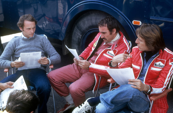 (L to R): Race winner Niki Lauda (AUT) discuses the official practice timing sheets with Ferrari team mate Clay Regazzoni (SUI), who finished third, and Luca di Montezemolo (ITA) Ferrari Team Manager. Swedish Grand Prix, Anderstorp, 8 June 1975. BEST IMAGE