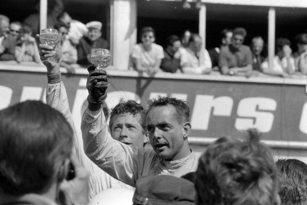 Olivier Gendebien and Phil Hill, 1st position, raise their glasses after the race.