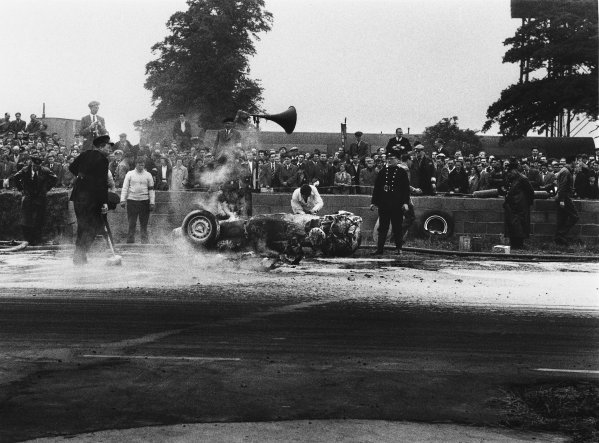 Silverstone, Great Britain. 14 July 1956.Tony Brooks's BRM P25 burns after he had crashed, action. World Copyright: LAT Photographic.Ref:  399 - 14.