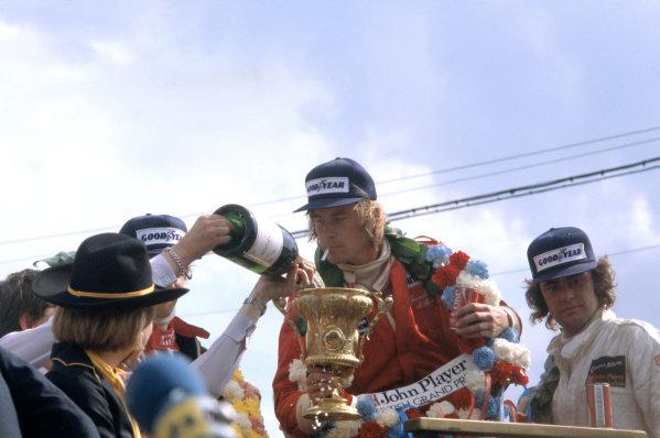 1977 Formula One World Championship British Grand Prix, Silverstone, England. 14th - 6th July. Winner James Hunt (McLaren) and Gunnar Nilsson (Lotus) celebrate on the podium. World Copyright: LAT Photographic. ref: 35mm Transparency 77 GB 25. 55mb Scan.