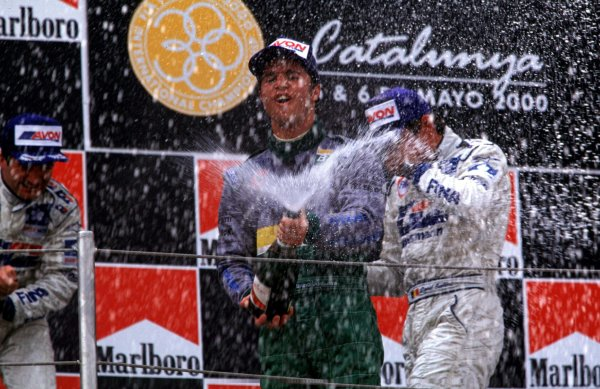 Race winner - Bruno Junqueira sprays the champagne, after winning the race. Podium Circuit de Catalunya, Spain, 5 May 2000. World - LAT Photographic