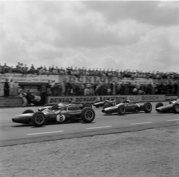 Jack Brabham, Brabham BT7 Climax, battles with Dan Gurney, Brabham BT7 Climax, who leads Bruce McLaren, Cooper T66 Climax, and a slow-starting Jim Clark, Lotus 25 Climax, at the start.