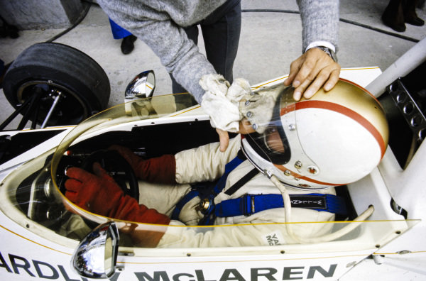 Mike Hailwood, McLaren M23 Ford, has his visor cleaned.