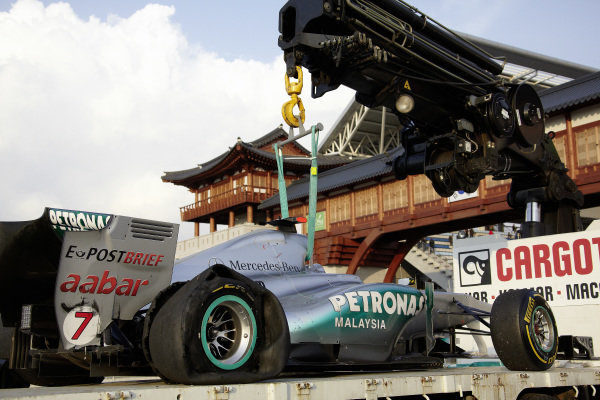 Michael Schumacher's Mercedes MGP W02 is returned to the garage.