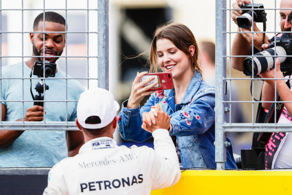 Circuit of the Americas, Austin, Texas, United States of America. Saturday 21 October 2017. Lewis Hamilton, Mercedes AMG, celebrates on the grid with a friend after securing pole. World Copyright: Zak Mauger/LAT Images  ref: Digital Image _56I1823