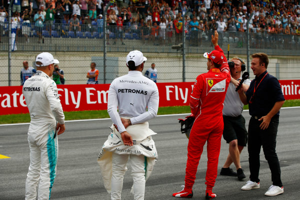 Red Bull Ring, Spielberg, Austria. Saturday 08 July 2017. Pole winner Valtteri Bottas, Mercedes AMG, stands to the left of Lewis Hamilton, Mercedes AMG, and waving second qualifier Sebastian Vettel, Ferrari. Pundit Davide Valsecchi conducts the post-qualifying interview. World Copyright: Andy Hone/LAT Images ref: Digital Image _ONY1503