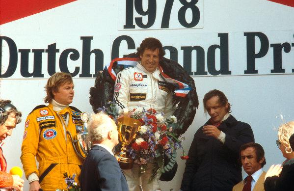 1978 Dutch Grand Prix.Zandvoort, Holland.25-27 August 1978.Mario Andretti (Team Lotus) 1st position, Ronnie Peterson (Team Lotus) 2nd position and Niki Lauda (Brabham Alfa Romeo) 3rd position on the podium. Ref-78 HOL 05.World Copyright - LAT Photographic