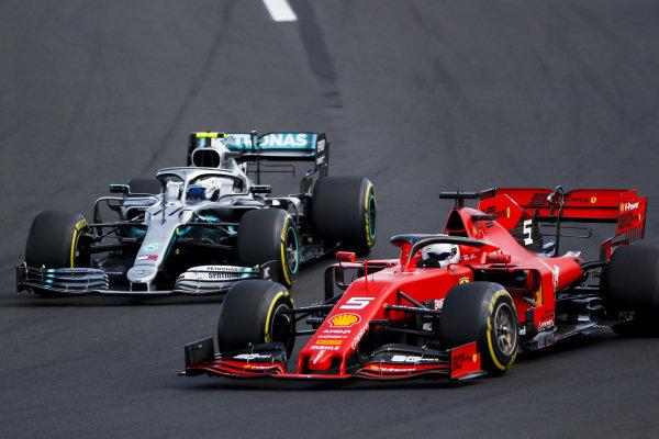 Sebastian Vettel, Ferrari SF90, passes Valtteri Bottas, Mercedes AMG W10, at the start