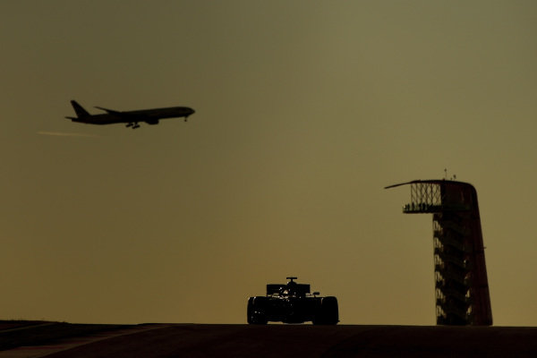 As a car approaches a Boeing 777-300 airliner lands in the background