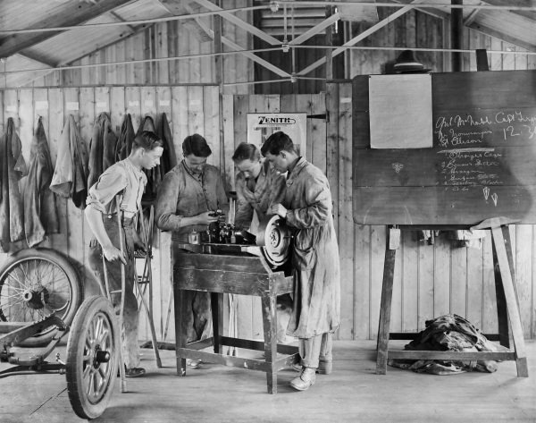 Wounded New Zealand soldiers examine a crankshaft as they are intstructed in the workshop of the Oatlands Park Hospital, Weybridge.
