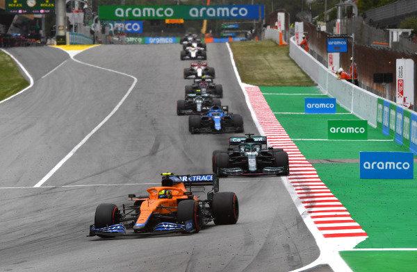 Lando Norris, McLaren MCL35M, leads Lance Stroll, Aston Martin AMR21, and Fernando Alonso, Alpine A521