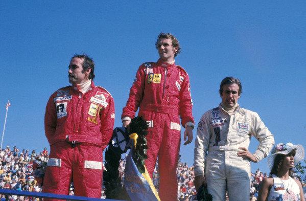 Clay Reggazoni, 3rd position, Niki Lauda, 1st position, and Carlos Reutemann, 2nd position, on the podium.
