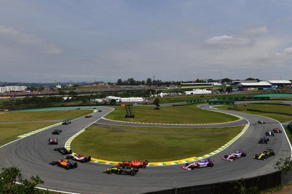 Kevin Magnussen, Haas VF-19, leads Antonio Giovinazzi, Alfa Romeo Racing C38, Lando Norris, McLaren MCL34, Daniel Ricciardo, Renault R.S.19, Charles Leclerc, Ferrari SF90, Lance Stroll, Racing Point RP19, Sergio Perez, Racing Point RP19, and the remainder of the field