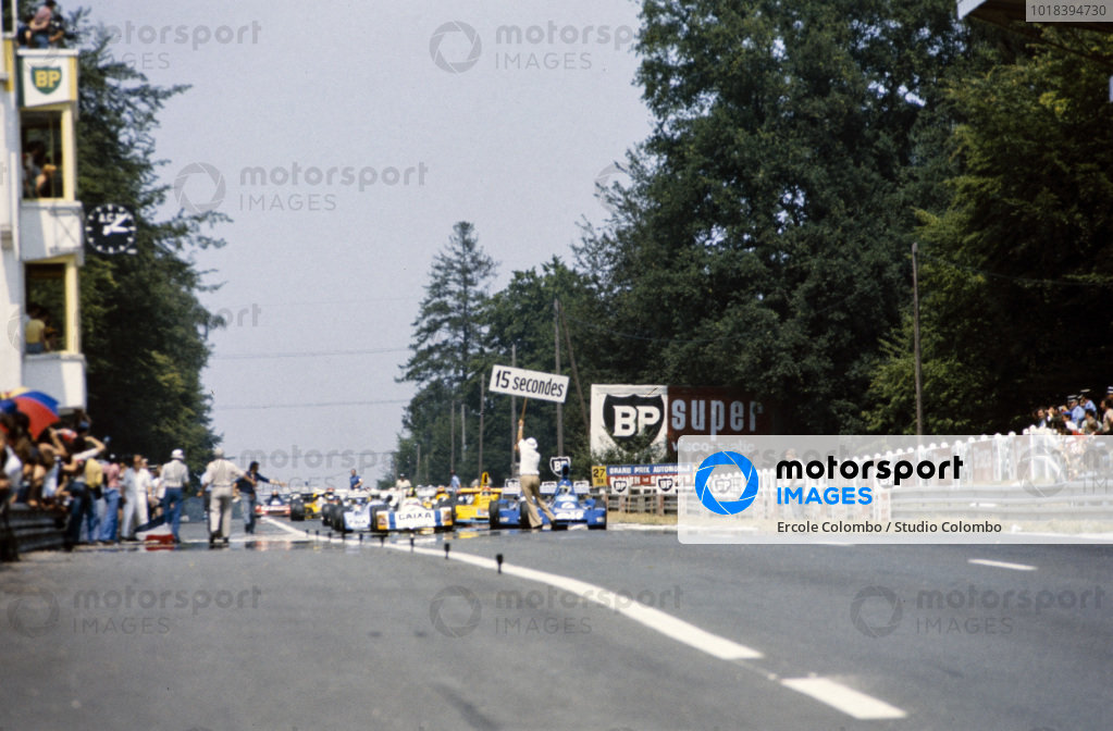 An official holds up a 15-second board ahead of the start. Patrick Tambay, Martini Mk19 Renault/Gordini, and Alex Ribeiro, March 762 BMW/Rosche, make up the front row.