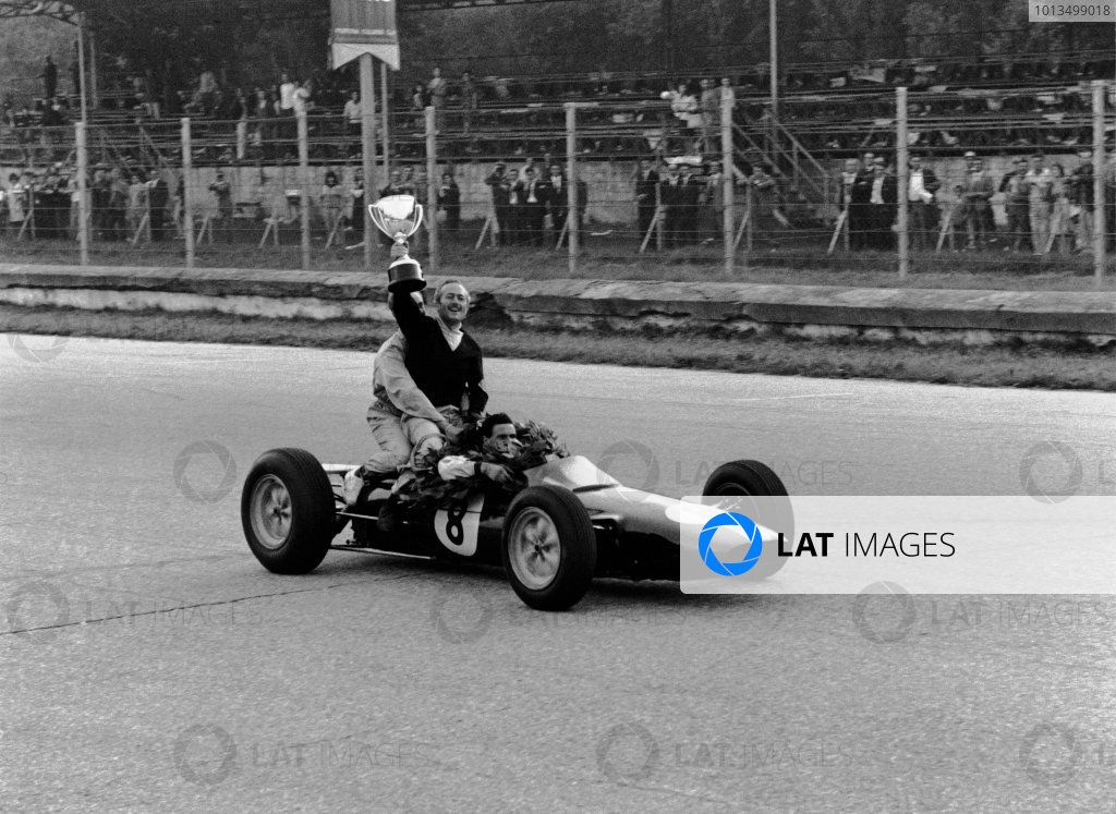 Monza, Italy.6-8 September 1963.Jim Clark (Lotus 25 Climax) gives team boss Colin Chapman a lift, as they celebrate finishing in 1st position and clinching the drivers and constructors World Championship titles.Ref-Autocar L63/282/35.World Copyright - LAT Photographic.