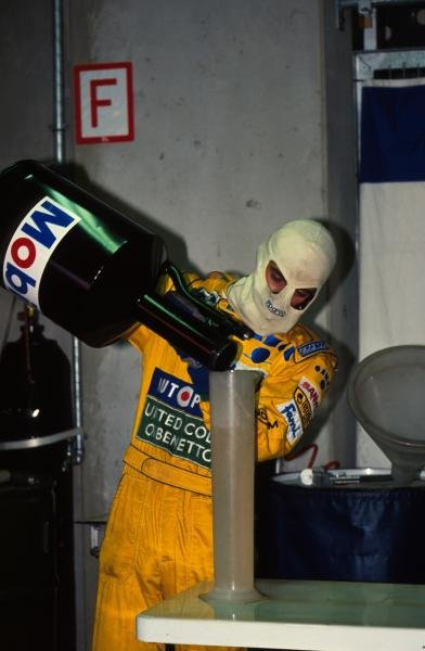 A Benetton mechanic measures out the race fuel.