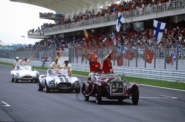 Sepang, Kuala Lumpur, Malaysia. 15-17 October 1999. Ferrari teammates Michael Schumacher and Eddie Irvine wave to the crowd in the pre-race drivers parade. Atmosphere. Ref: 99MAL50. World Copyright - LAT Photographic