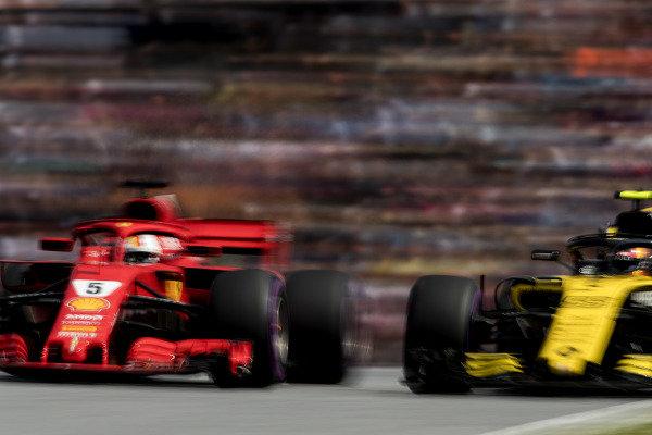 Sebastian Vettel, Ferrari SF71H, is passed by Carlos Sainz Jr., Renault Sport F1 Team R.S. 18.