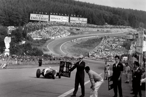 1960 Belgian Grand Prix.Spa-Francorchamps, Belgium. 19 June 1960.Jack Brabham, Cooper T53-Climax, 1st position, passes the pits. John Cooper (bending down) studies the tyres as Brabham passes, action.World Copyright: LAT PhotographicRef: Autosport b&w print. Published: Autosport, 24/6/1960 front cover