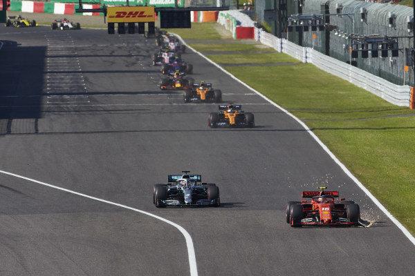 Charles Leclerc, Ferrari SF90, drags a sparking front wing endplate, ahead of Lewis Hamilton, Mercedes AMG F1 W10 and Carlos Sainz Jr., McLaren MCL34