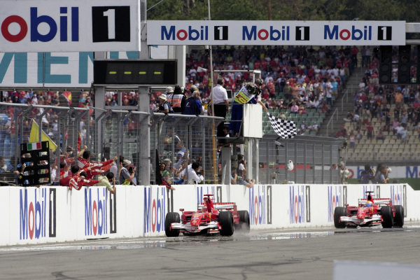 Michael Schumacher, Ferrari 248 F1 celebrates with his team as he takes the chequered flag for victory with teammate Felipe Massa behind in 2nd.