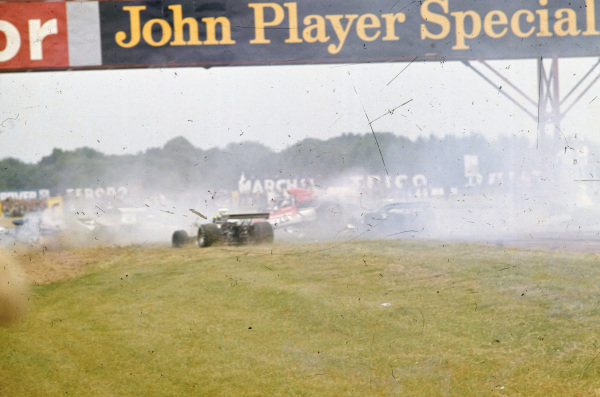 A multi-car pile-up, triggered after Jody Scheckter spun his McLaren M23. Jean-Pierre Beltoise, BRM P160E, is sideways in the middle of the pack with his rear wheels in the air. Wilson Fittipaldi, Brabham BT42 Ford, is to the left of him. On the far left, Carlos Pace crashes his Surtees TS14A Ford.