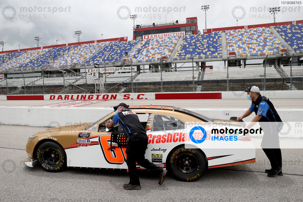 Crew members push the car of Stephen Leicht, Motorsports Business Management Toyota through the garage area, Copyright: Chris Graythen/Getty Images.