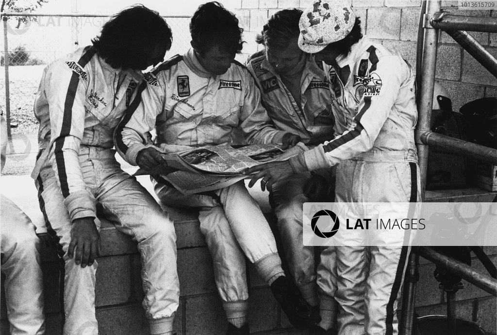 Watkins Glen, New York State, USA. 22nd July 1972. Rd 11.Tim Schenken sits with Brian Redman, reading Motoring News with Ronnie Peterson and Arturo Merzario looking on in the pits, portrait. World Copyright: LAT Photographic.Ref: 4673 - 16.