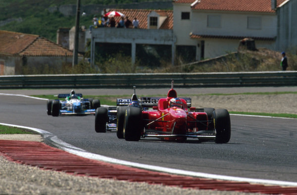 Estoril, Portugal.20-22 September 1996.Michael Schumacher (Ferrari F310) is followed by Jacques Villeneuve (Williams FW18 Renault) and Gerhard Berger (Benetton B196 Renault) early on in the race.Ref-96 POR 09.World Copyright - LAT Photographic
