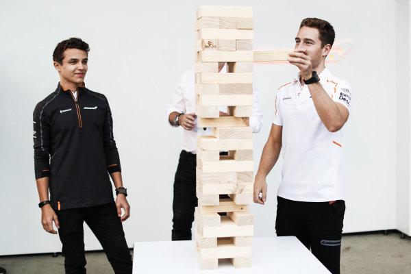 Stoffel Vandoorne, McLaren, plays a game of giant Jenga with Lando Norris, McLaren