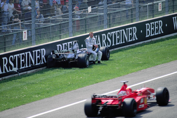 Mika Hakkinen, McLaren MP4-14, after crashing out of the race, is passed by Michael Schumacher, Ferrari F399.