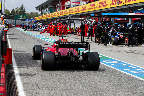Charles Leclerc, Ferrari SF21, passes Fernando Alonso, Alpine A521, in the pits