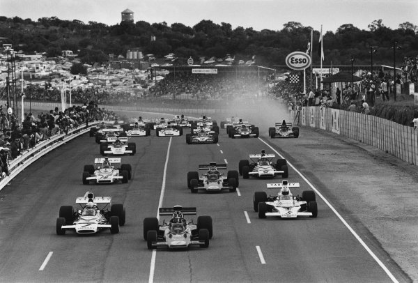 Kyalami, South Africa. 3rd March 1973.Emerson Fittipaldi (#1 Lotus 72D-Ford Cosworth), 3rd position, leads Jody Scheckter (McLaren M19C-Ford), retired, Denny Hulme (McLaren M23-Ford), 5th position and Ronnie Peterson (#2 Lotus 72D-Ford Cosworth), retired, at the start of the race, action. World Copyright: LAT Photographic.Ref:  5092 - 12