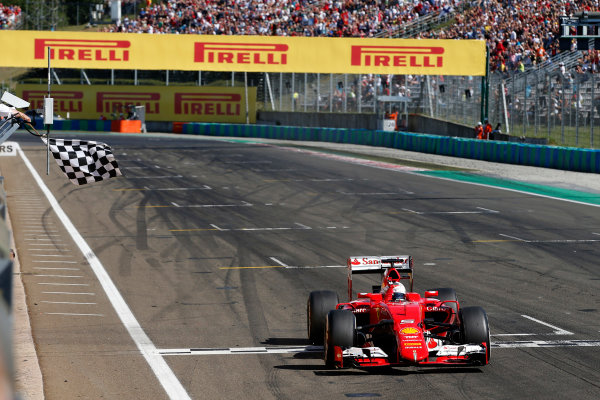 Hungaroring, Budapest, Hungary. Sunday 26 July 2015. Sebastian Vettel, Ferrari SF15-T, crosses the line to take the chequered flag and the win. World Copyright: Glenn Dunbar/LAT Photographic ref: Digital Image _89P8837