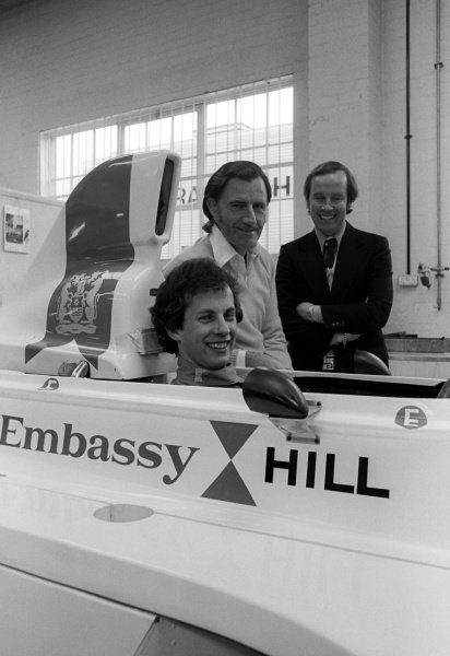 Tony Brise (GBR) sits in the Embassy Hill Racing GH1 alongside his boss Graham Hill (GBR) at the team headquarters.