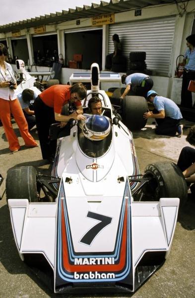 Bernie Ecclestone (GBR) F1 Supremo manages a smirk as a deadly serious Carlos Reutemann (ARG) Brabham BT44B ponders on his eighth place finish. Brazilian Grand Prix, Interlagos, Sao Paulo, 26 January 1975. BEST IMAGE