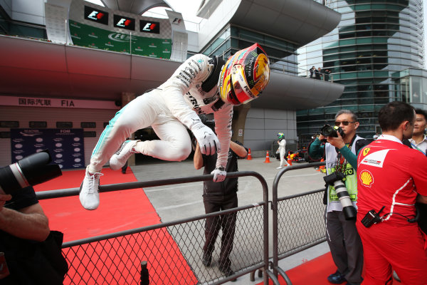 Shanghai International Circuit, Shanghai, China.  Saturday 08 April 2017.  Lewis Hamilton, Mercedes AMG, leaps over a fence in parc ferme after taking pole position. World Copyright: Charles Coates/LAT Images  ref: Digital Image AN7T8988