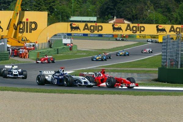 Race winner Michael Schumacher (GER) Ferrari F2004 and Juan Pablo Montoya (COL) Williams FW26 go side by side on lap one. Formula One World Championship, Rd4, San Marino Grand Prix, Race Day, Imola, Italy, 25 April 2004. DIGITAL IMAGE BEST IMAGE