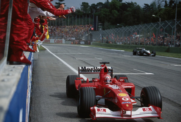 Michael Schumacher, Ferrari F2002, raises his arm in victory as he passes his cheering mechanics.