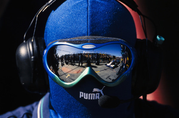 The Sauber team, reflected in the goggles of this team member, prepare for a practice pitstop.