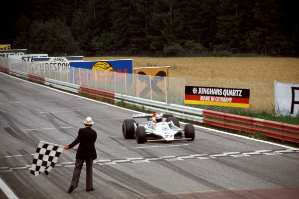 Alan Jones, Williams FW07 Ford takes the chequered flag for victory.