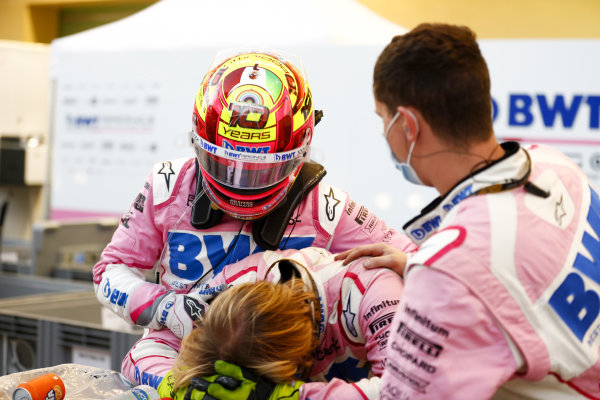 Sergio Perez, Racing Point, comiserates with his mechanics after retiring from the race