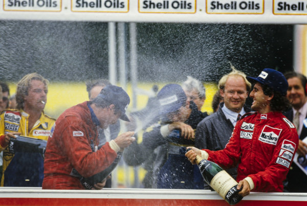 Nigel Mansell, 1st position, newly-crowned world champion Alain Prost, 4th position, Ayrton Senna, 2nd position, and Keke Rosberg with a cigarette in his mouth, 3rd position, spray champagne on the podium.