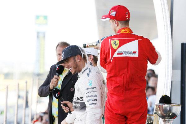 Suzuka Circuit, Suzuka, Japan.  Sunday 27 September 2015. Sebastian Vettel, Ferrari, 3rd Position, pours Champagne on Lewis Hamilton, Mercedes AMG, 1st Position. World Copyright: Steven Tee/LAT Photographic ref: Digital Image _X0W2100