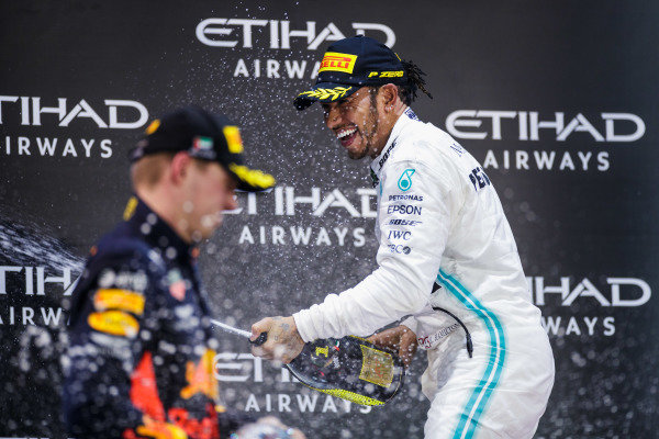 Lewis Hamilton, Mercedes AMG F1, 1st position, and Max Verstappen, Red Bull Racing, 2nd position, celebrate on the podium with Champagne