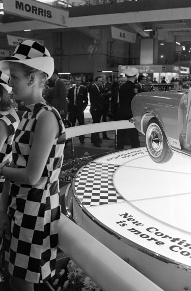 A model wears a chequer pattern outfit in front of the Mk II Ford cortina display.