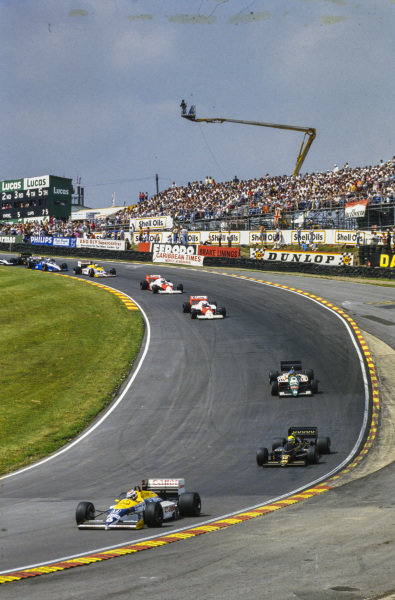 Nelson Piquet, Williams FW11 Honda, leads Ayrton Senna, Lotus 98T Renault, Gerhard Berger, Benetton B186 BMW, Alain Prost, McLaren MP4-2C TAG, Keke Rosberg, McLaren MP4-2C TAG, and Nigel Mansell, Williams FW11 Honda, through Paddock Hill Bend.